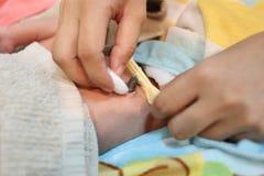 Bebé asiático en la limpieza del ombligo después de bañar Foto de archivo