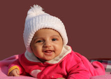 Bebé asiático feliz no tampão branco do inverno Imagem de Stock