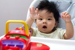 Bebé asiático pequeno na cadeira elevada Imagens de Stock Royalty Free