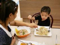 Bebé asiático que coge un beansprout de su comida y que negocia con la mamá para no comerla fotos de archivo libres de regalías
