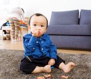 Bebé asiático que come el caramelo foto de archivo