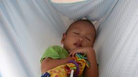 Bebé asiático que duerme en el oscilación de la cuna almacen de video