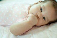 Bebé asiático que pone en cama Imagen de archivo