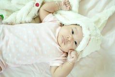 Bebé asiático que pone en cama Fotos de archivo