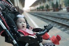 Bebé asiático que se sienta en cochecito en el ferrocarril Imagenes de archivo