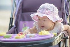 Bebé asiático que se sienta y que juega en cochecito en un paseo Imágenes de archivo libres de regalías
