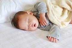 Bebé asiático recién nacido pacífico que duerme en cama con la manta fotos de archivo libres de regalías