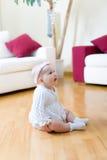 Bebé assentado em um assoalho fotografia de stock royalty free