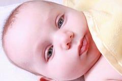 Bebé bajo la manta amarilla Imagen de archivo