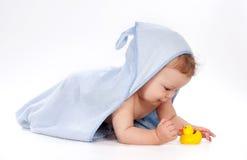 Bebé bajo la toalla que juega con el pato de goma Imagenes de archivo