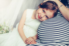 Bebé bastante joven que sonríe cerca de madre embarazada Imagen de archivo