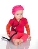 Bebê pequeno com o phonendoscope que senta-se em um fundo branco Foto de Stock