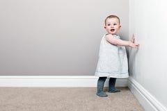 Bebé bonito de encontro à parede fotografia de stock