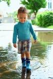 Bebé bonito que anda através da poça Fotos de Stock