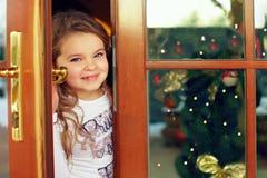 Bebé bonito que olha para fora da porta Fotografia de Stock Royalty Free