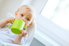 Bebé bonito que se sienta en silla y que bebe de la taza Imágenes de archivo libres de regalías