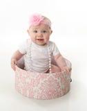 Bebé bonito que se sienta en un hatbox Imagenes de archivo