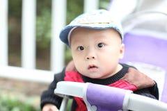 Bebé bonito que senta-se no carrinho de criança foto de stock