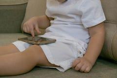 Bebé casual que se sienta en un sofá en casa que juega y que toca un teléfono móvil Foto de archivo libre de regalías
