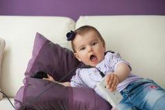 Bebé casual que se sienta en un sofá en casa que juega y que toca un teléfono móvil Imagenes de archivo