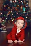 Bebé cerca por el árbol del Año Nuevo, días de fiesta de la Navidad Foto de archivo