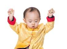 Bebé chino que se sostiene con el bloque de madera del juguete foto de archivo