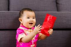 Bebé chino tan feliz para el bolsillo rojo Fotos de archivo