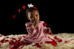Bebé coberto com os pedais cor-de-rosa Foto de Stock