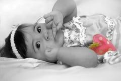 Bebé com o dedo em suas boca e morango Imagens de Stock Royalty Free