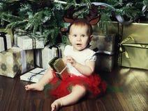 Bebé con el árbol de navidad de adornamiento cercano de la caja de regalo Imagen de archivo libre de regalías