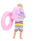Bebé con el anillo inflable que oculta detrás de bola Fotografía de archivo