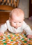 Bebé con el arrastre de los ojos azules foto de archivo