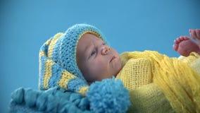 Bebé con el casquillo con una borla que miente pacífico metrajes
