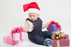 Bebé con el casquillo de la Navidad que se sienta con los regalos Foto de archivo libre de regalías