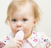 Bebé con el cepillo para el pelo para el pelo. Imagen de archivo