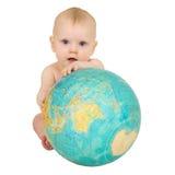Bebé con el globo geográfico aislado en blanco Imagen de archivo