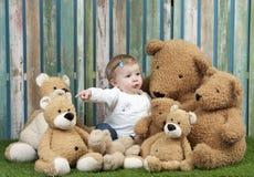 Bebé con el grupo de osos de peluche, asentado en hierba Fotos de archivo libres de regalías