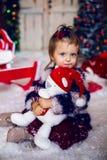 Bebé con el juguete del oso de peluche en un casquillo rojo en el Año Nuevo en casa Fotografía de archivo