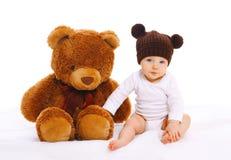Bebé con el juguete grande del oso de peluche en blanco Imagenes de archivo