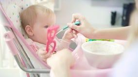 Bebé con el juguete que se sienta en silla y que come el puré Bebé que introduce de la madre con la cuchara metrajes