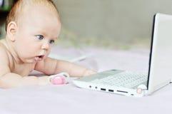 Bebé con el ordenador portátil en casa Foto de archivo libre de regalías