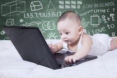 Bebé con el ordenador portátil y garabatos Fotografía de archivo