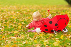 Bebé con el paraguas rojo que recoge las hojas caidas Foto de archivo