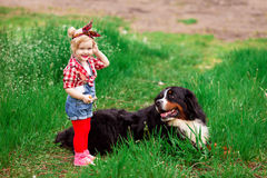 Bebé con el perro Berna en jardín de la primavera Fotos de archivo