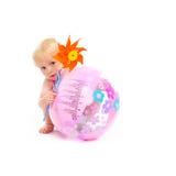 Bebé con el pinwheel que oculta detrás de bola de playa Fotos de archivo libres de regalías