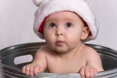 Bebé con el sombrero de Santa que se sienta en lavabo de colada Fotografía de archivo