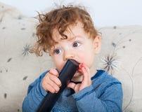 Bebé con el telecontrol Fotografía de archivo