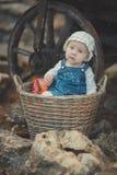 Bebé con el vestido blanco que lleva profundo de los ojos azules del océano y de la camisa y de los vaqueros de la mejilla rosada Fotografía de archivo libre de regalías