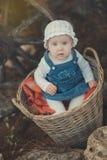 Bebé con el vestido blanco que lleva profundo de los ojos azules del océano y de la camisa y de los vaqueros de la mejilla rosada Imagen de archivo