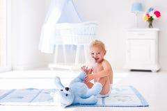 Bebé con la botella de leche en cuarto de niños soleado Imagen de archivo libre de regalías